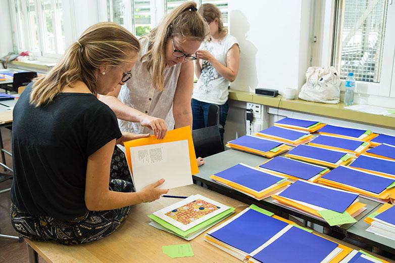 Alles Handarbeit: Studentinnen begutachten fertige Musterbuch-Seiten Bild: Hochschule Luzern/Priska Ketterer